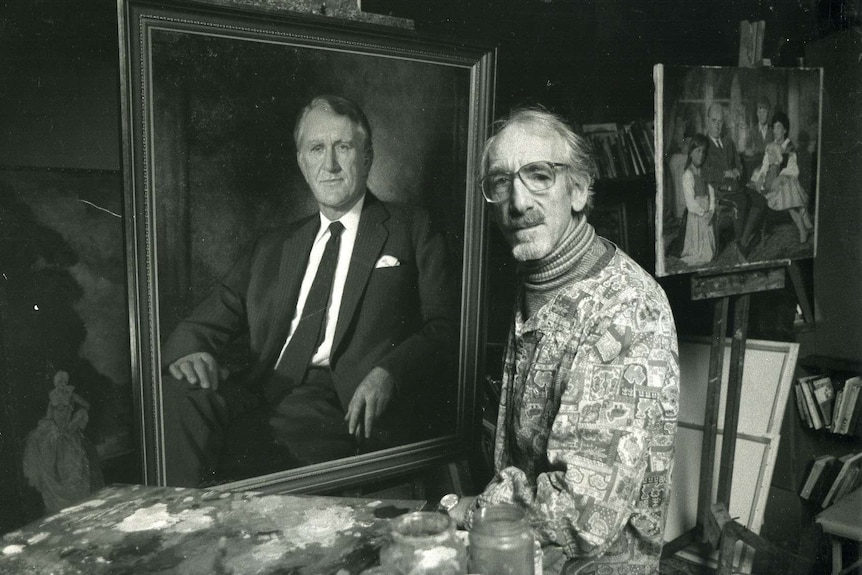 A black and white photo of painter Paul Fitzgerald standing next to a painting of Malcolm Fraser.