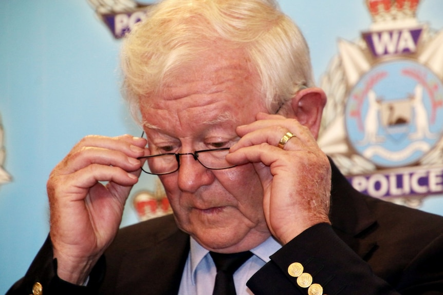 A close-up photo of Denis Glennon adjusting his reading glasses in front of a police backdrop.