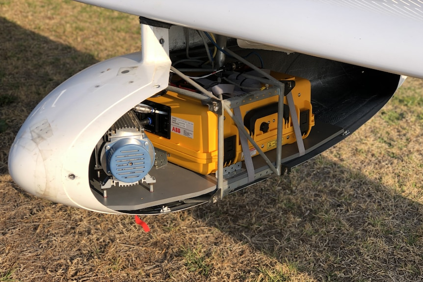 A small machine attached underneath the wing of an aircraft.