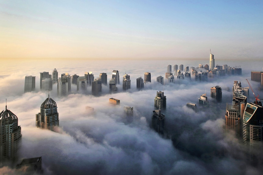The tops of high-rise buildings in Dubai poke out of a heavy cloud covering the city