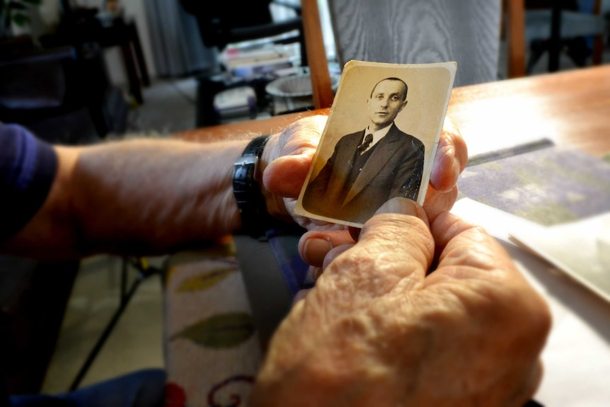 Andy Factor holds an old photo of his father, Charles.