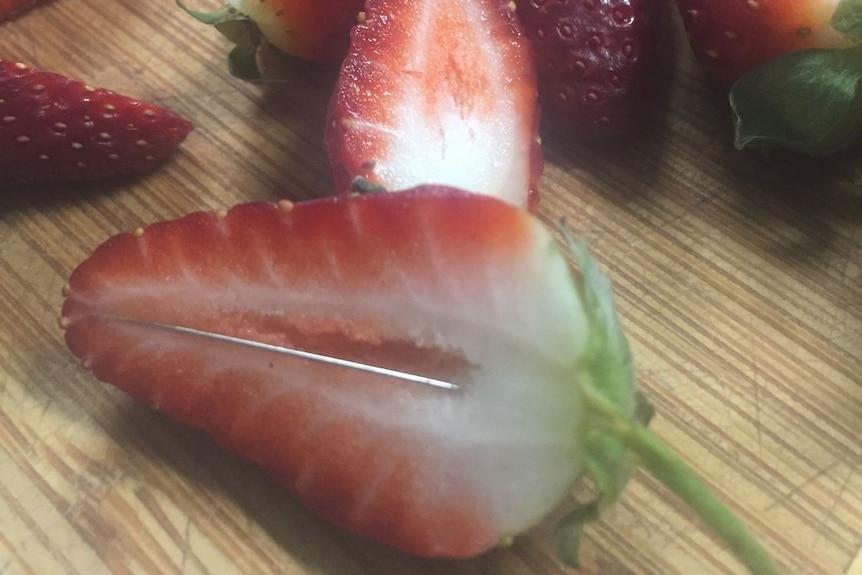 A strawberry cut in half with a needle in it.
