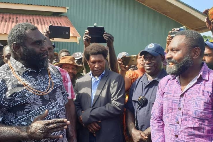 Ishmael Toroama speaks to another man while people film and watch on.