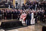 A military honour guard carries the casket of former Senator John McCain into the US Capitol Rotunda.