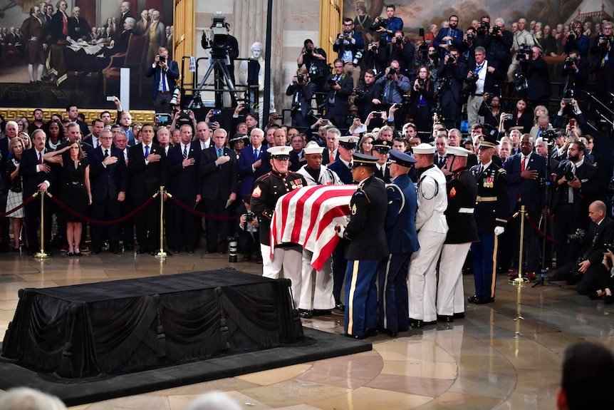 A military honour guard carries the casket of former Senator John McCain into the US Capitol Rotunda.