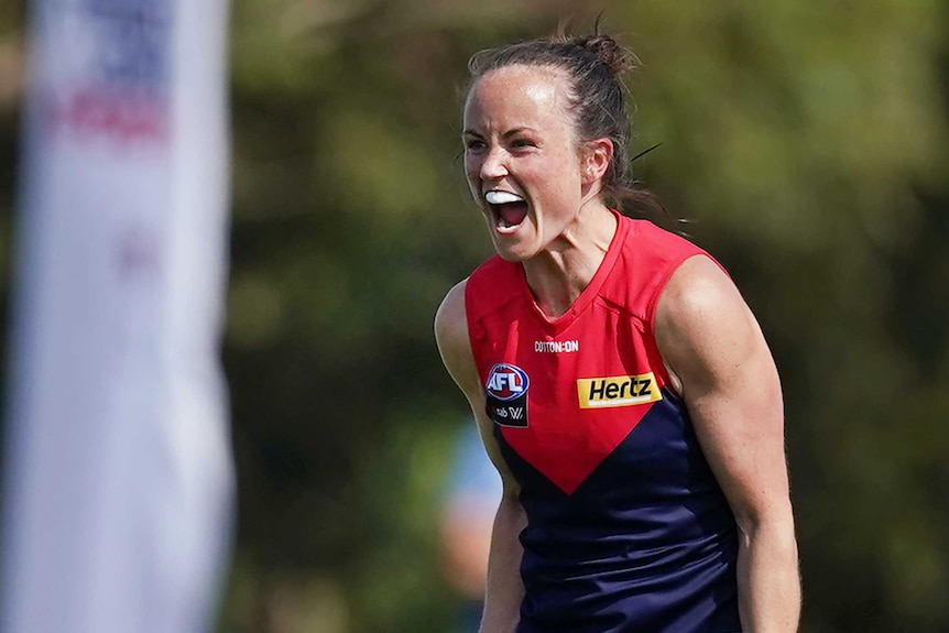 A Melbourne Demons AFLW player yells out as she celebrates her team winning a match.