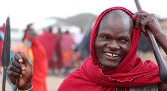 Tanzanian man wearing a red and black scarf stands in a market place