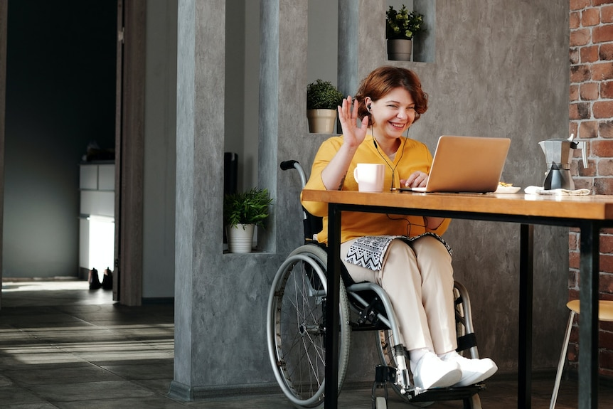 A woman in a wheelchair uses her laptop computer