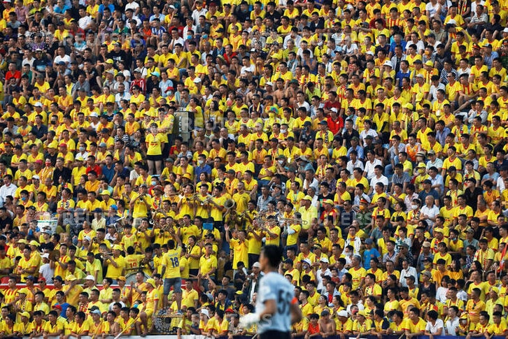 Thousands of fans pictured watching the soccer match, wearing yellow shirts and team colours.