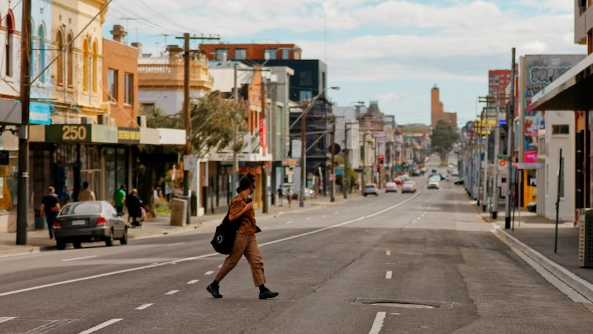 A person wearing an orange shirt and tan pants walks across an inner-city street. Very few people or cars around