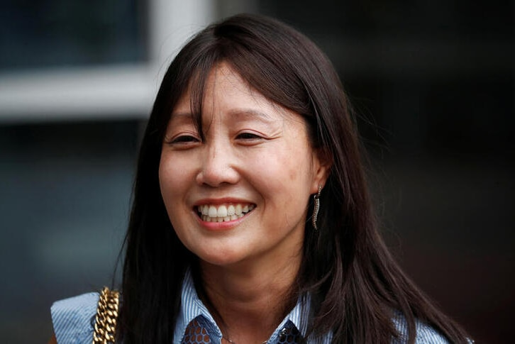 A photo of Kara Bos smiling after attending her trial in front of a court in Seoul, South Korea.