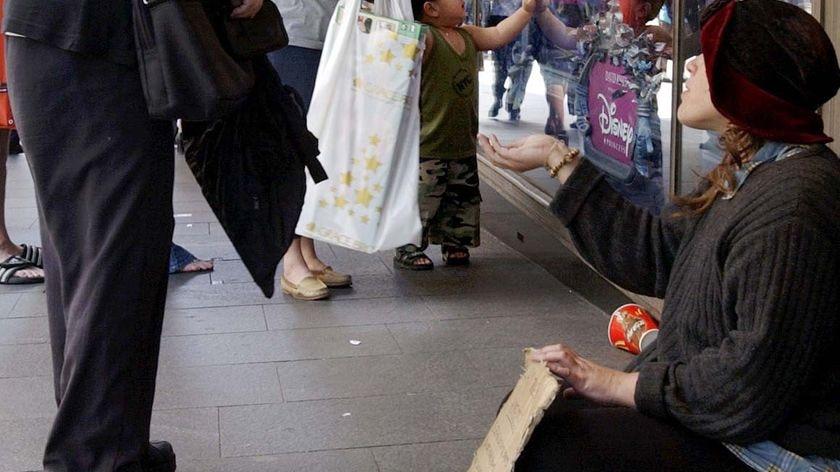 A homeless woman asks for money on a Sydney street.