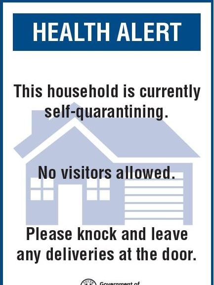 A blue and white sign reading 'Health alert: This house is currently self-quarantining. No visitors allowed.'