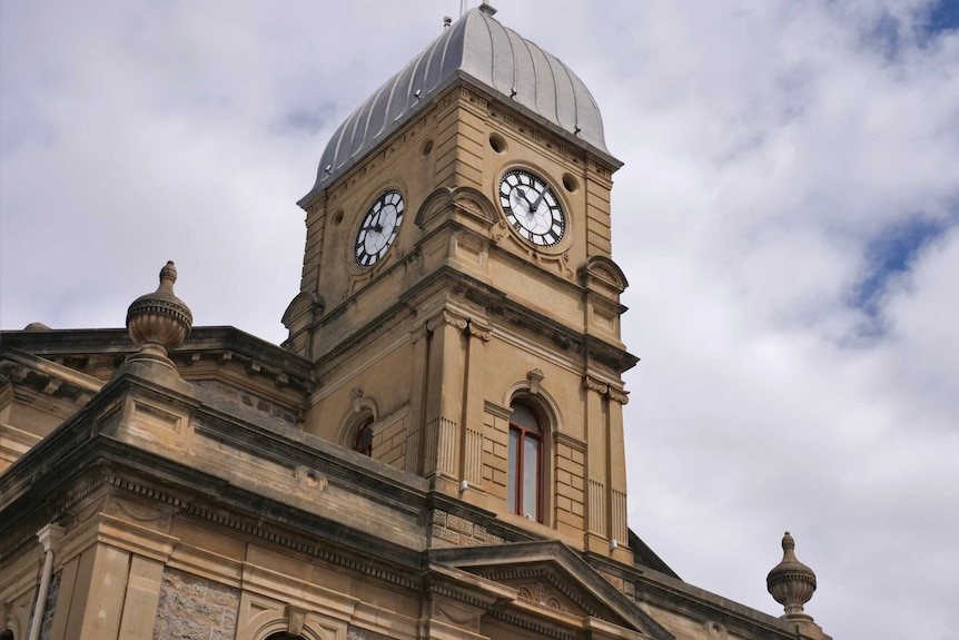 A town hall clock tower under a cloudy sky.