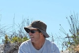 A man wearing a white t-shirt, hat and sunglasses sits in front of a sand dune laughing with a beer.