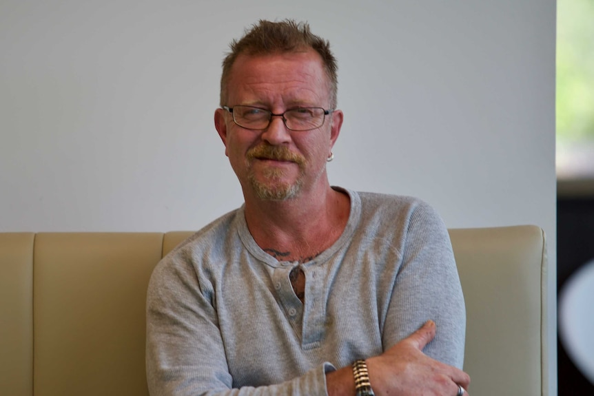 Andrew Hodson sits on a couch with his arms folded, wearing a half smirk.