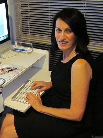 A woman sitting at a computer, about to type and looking at the camera.
