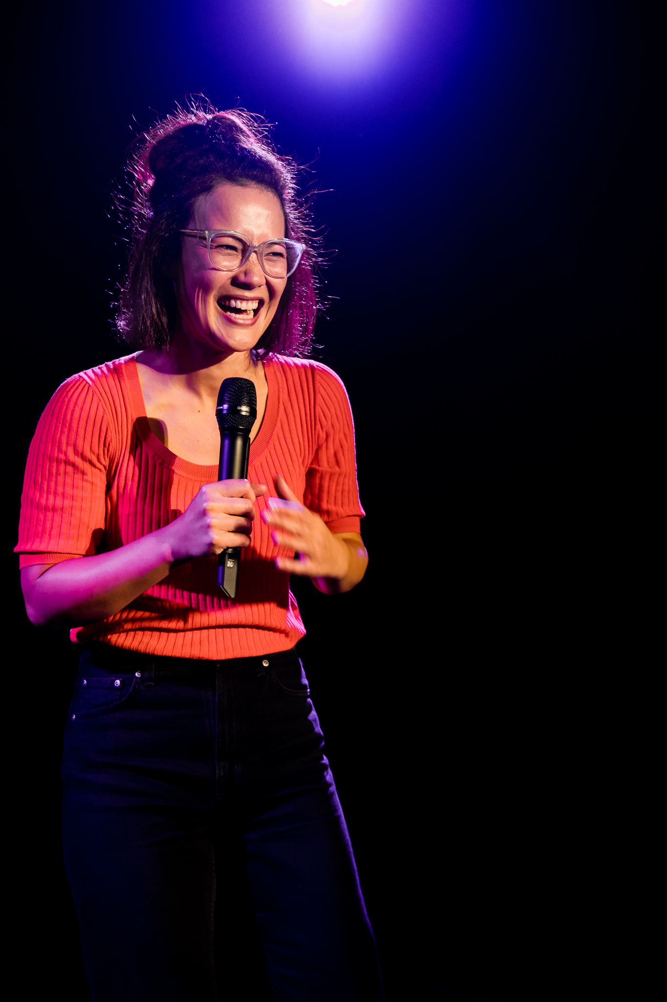 A smiling 30-something Asian Australian woman is on stage in a dark theatre. She's wearing glasses and holding a microphone.