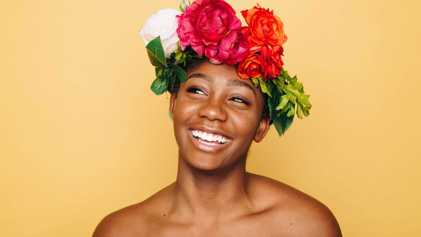 Closeup of woman smiling wearing flower crown with a bright yellow backdrop to represent simple skincare routines