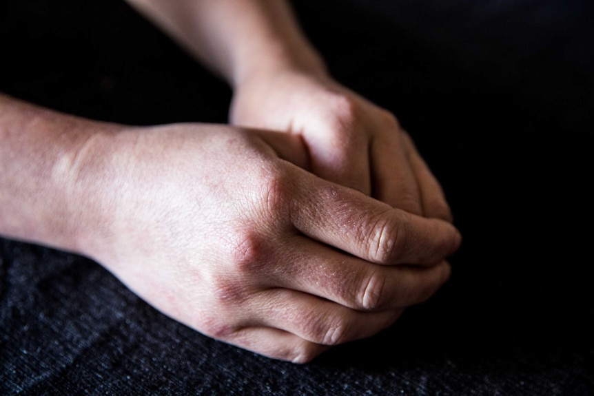 A person's hands sit in their lap, one folded over the other.