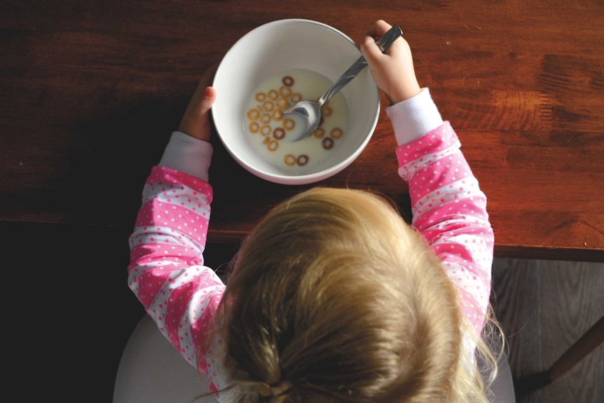Girl eating cereal at a table.