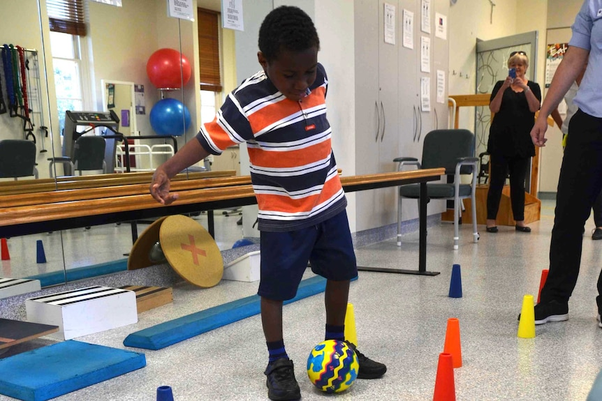 Edward, from PNG kicks the soccer ball around cones.