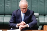 Malcolm Turnbull glances down to his left wrist and adjusts his watch with his right hand.
