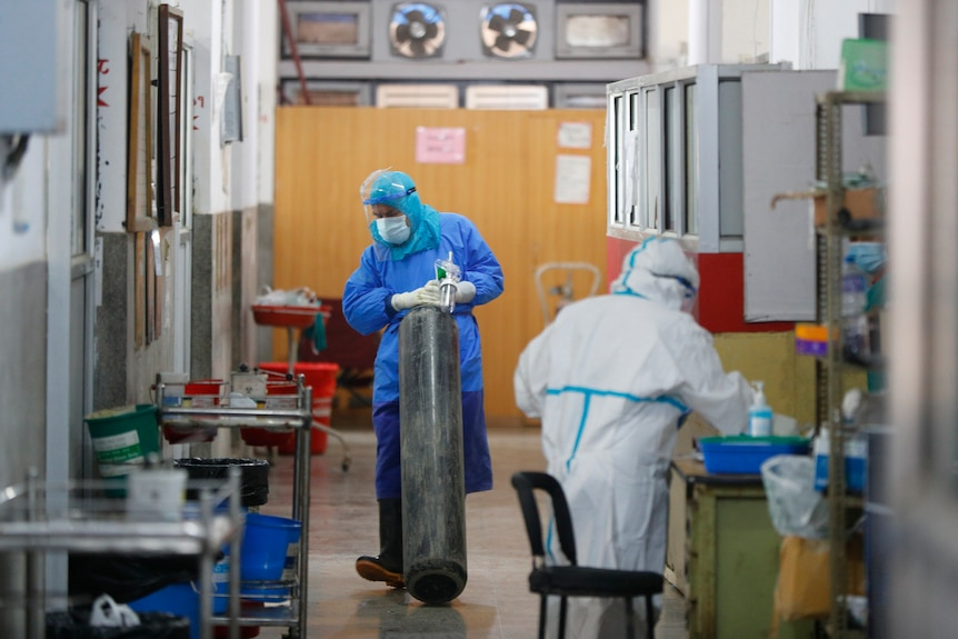 A Nepalese health worker in protective gear drags oxygen cylinder inside a COVID-19 ward.