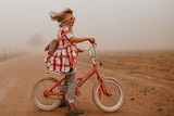 Small girl on a pink bike wearing goggles stand defiantly in dust storm