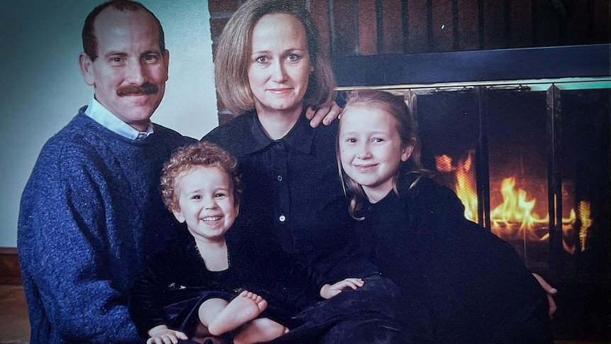 A family portrait of a man and woman with two girls on their laps in front of a fireplace