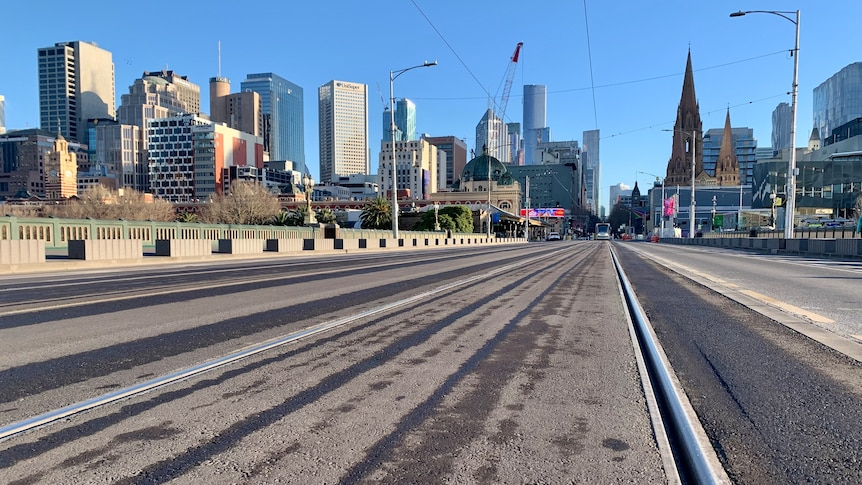 A low-angled photograph of the tram tracks running over Princes Bridge, viewed from Southbank with CBD visible.