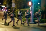 Police holding large guns run.