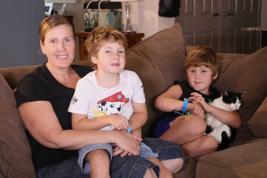 A mother sits on a brown sofa at home smiling with her two sons, aged 6 and 7.