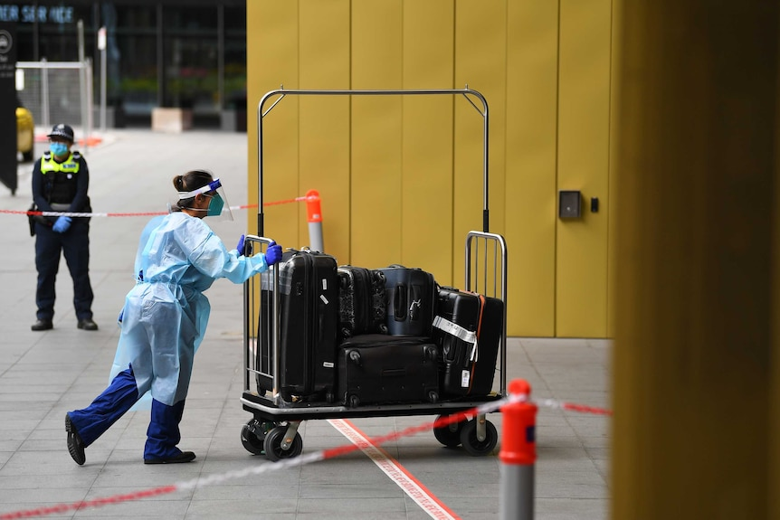A healthcare worker in full PPE pushes luggage into a hotel.