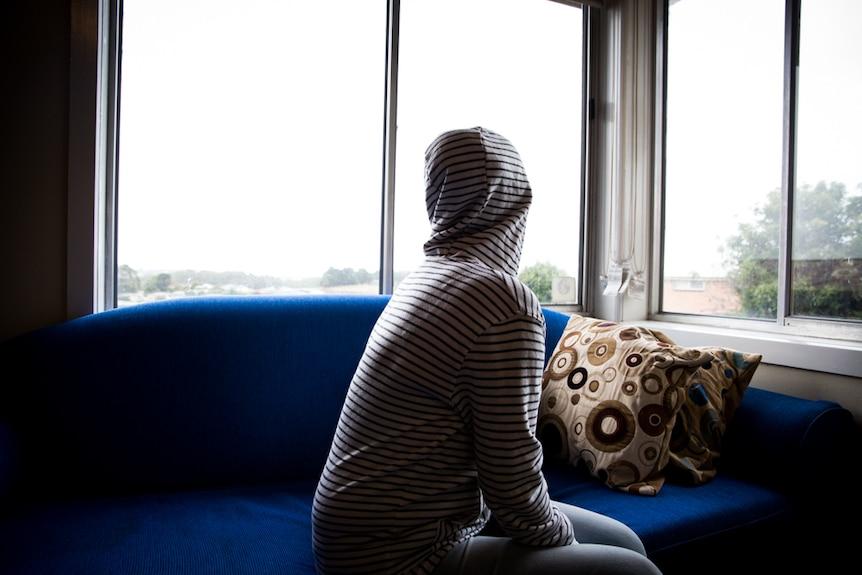 Mary sits on a couch in Burnie, regional Tasmania