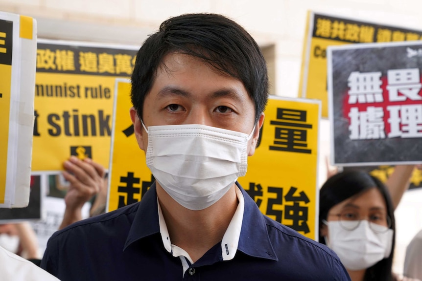 A man in a dark blue shirt and white face mask surrounded by protesters holding yellow signs