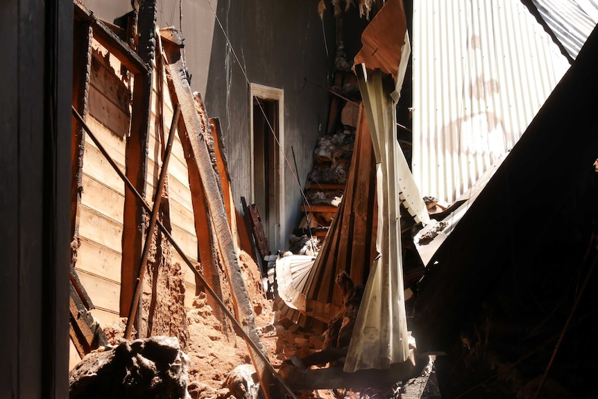 A roof fallen into a burnt and destroyed room following a hose fire