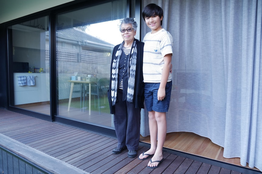 A grandmother and her grandson in front of their house