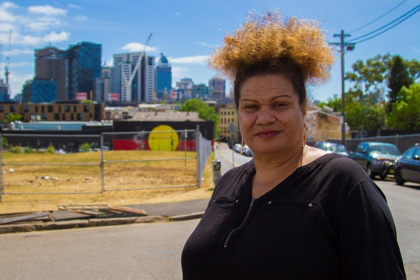 Dixie pictured with Aboriginal flag mural in Redfern