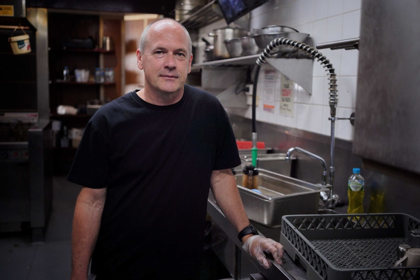 Former pilot Matt Purton stands at the sink in the kitchen of the cafe where he now works.
