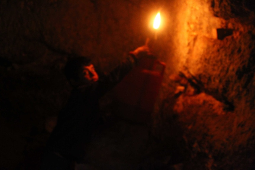 A boy holds a lamp in a cave-like room.