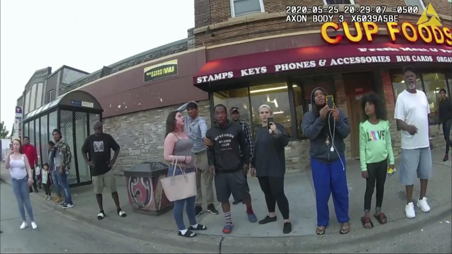 Bystanders filming police officer as he presses his knee on George Floyd's neck.