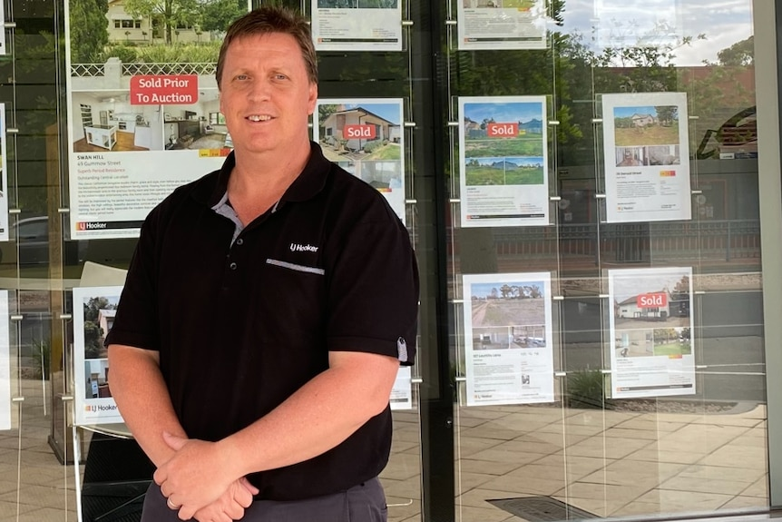 Real estate agent standing out the front of his shop smiling with property ads in the background