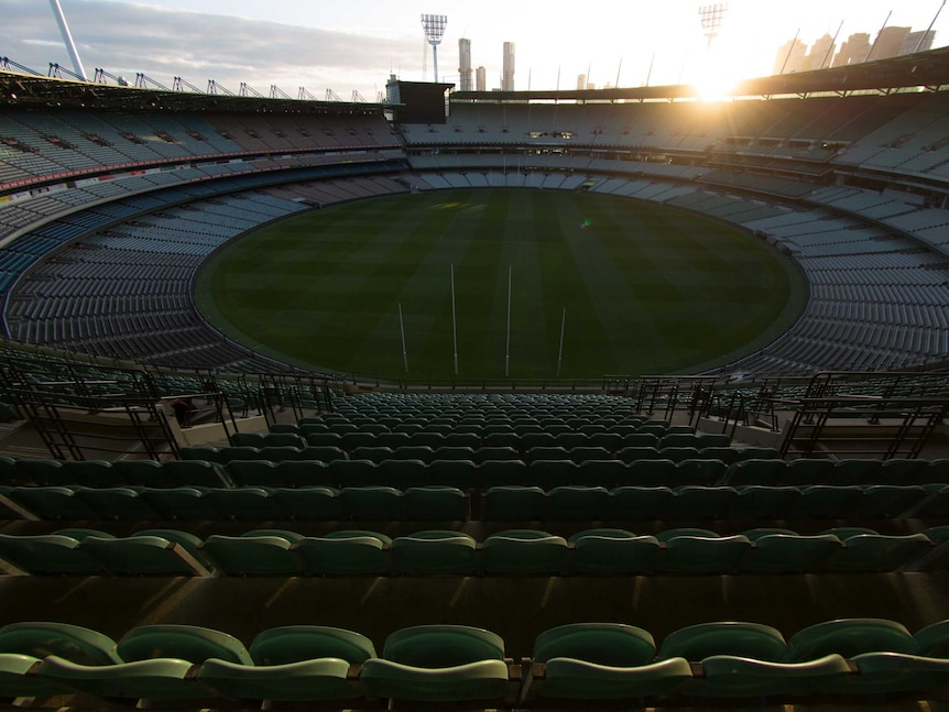 The sun goes down behind the Melbourne Cricket Ground light towers and city buildings