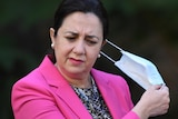 Queensland Premier Annastacia Palaszczuk in a pink suit pulls off her face mask.