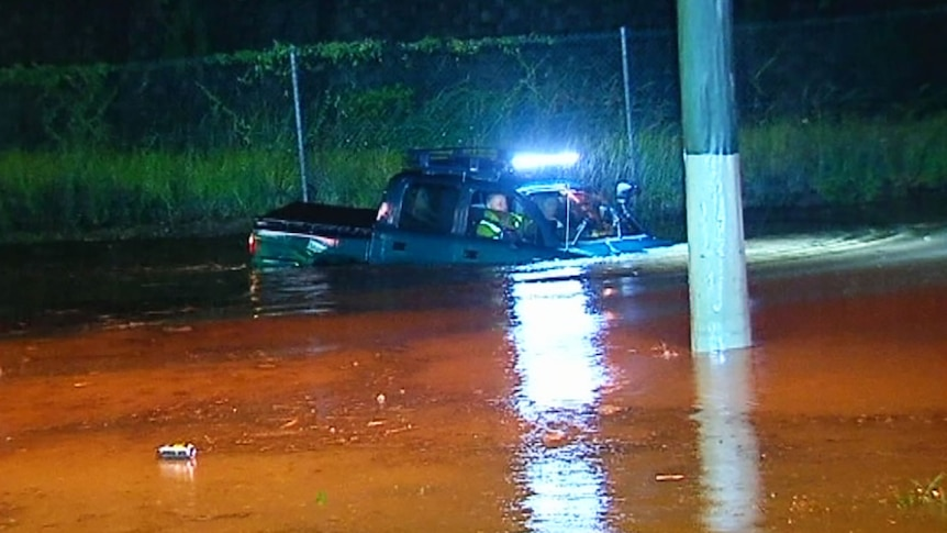 A man drives his four-wheel drive onto a closed road in flood at Helensvale.