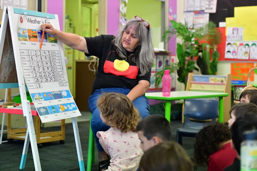 A woman in an Aboriginal flag t-shirt points to a calendar on an a-frame as children in a brightly coloured classroom look on.