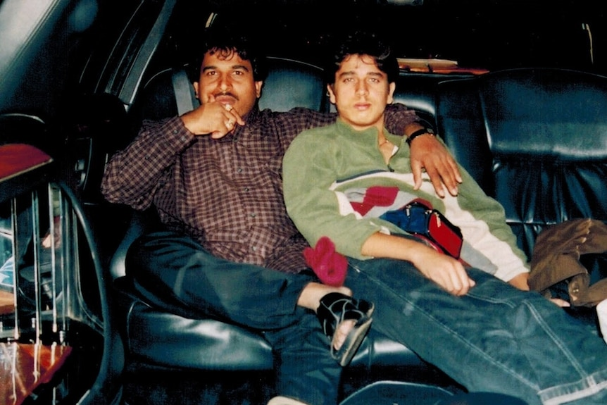 Vick Singh sits, right, in a car next to his uncle, left, who has his arm around him. It appears to be a film photo.