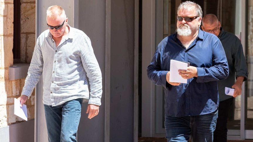Two men walk out of a court building wearing collared shirts and sunglasses.