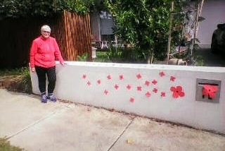 A woman wears a pink jumper and stands next to paper poppies taped to her fence.